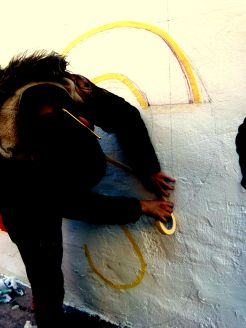 Un dels alumnes envoltant la S d'aspiracions de cinta abans de pintar-la